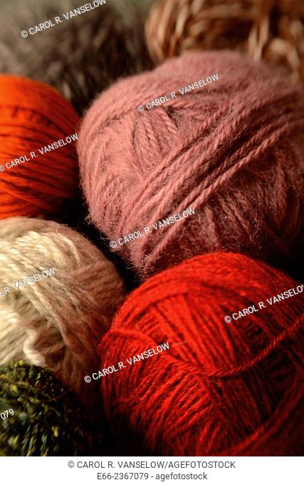 Closeup shot of balls of yarn in various colours - orange, white, green, lavender, grey