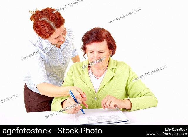 young woman helping senior woman to write a letter