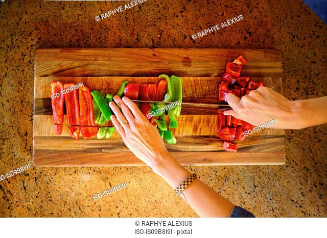 Overhead view of woman's hands chopping red and green peppers