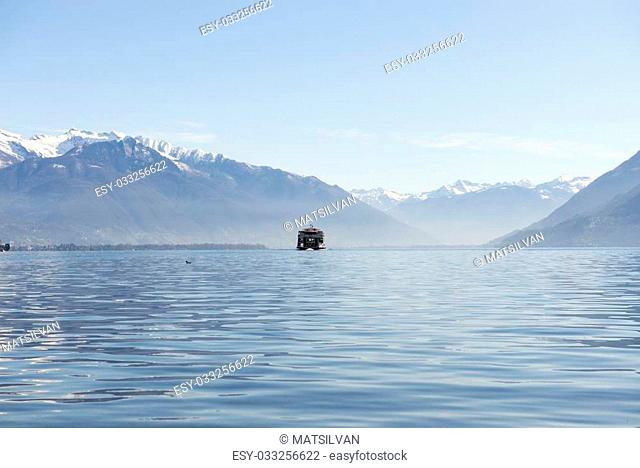 Passenger ship on an alpine lake with snow-capped mountain
