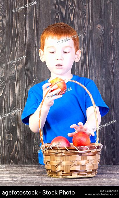the boy looks at the nectarine, which is in his hand, there is a basket on the table with other nectarines and peaches