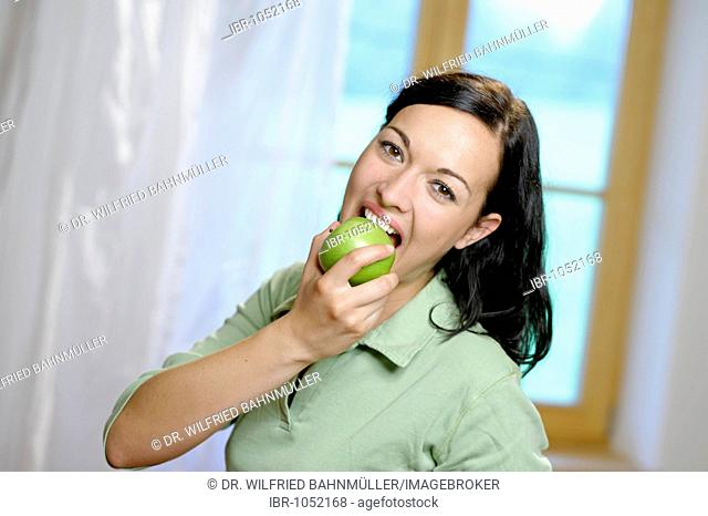 Woman taking a large bite from a green apple, healthy diet