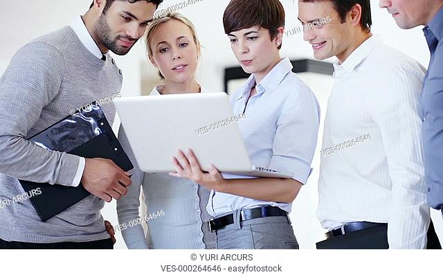 Five businesspeople looking at a laptop and reacting in a pleased manner