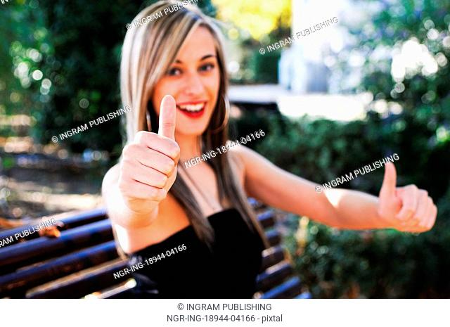 Pretty girl sitting in a bench in the park showing thumb up sign
