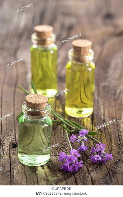 lavender oil in a glass bottle on a wooden background