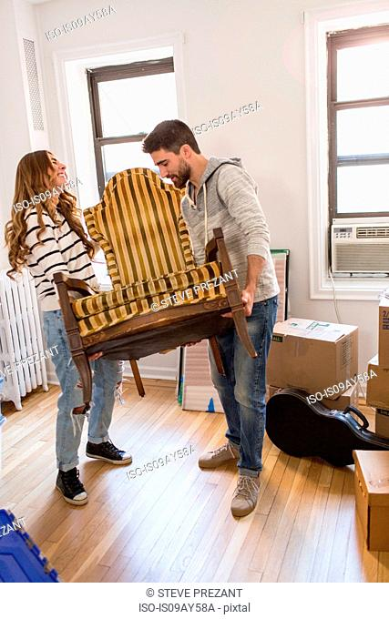 Moving house: Young couple lifting chair