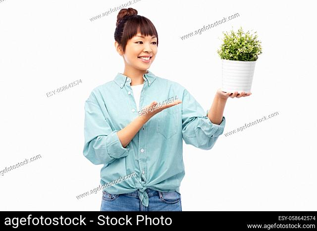 happy smiling asian woman holding flower in pot