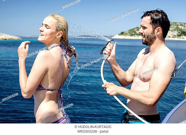Woman being sprayed with water on sailboat, Adriatic Sea