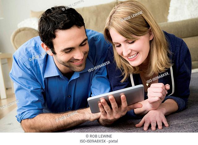 Young couple lying on floor with electronic book