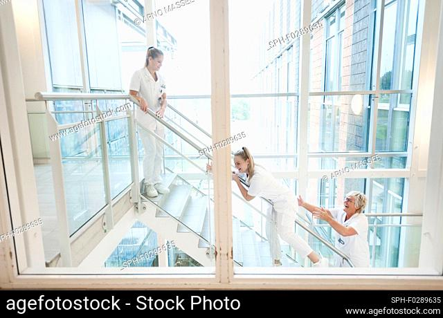 Nurses laughing and sliding down the stairs in the stairwell of a hospital