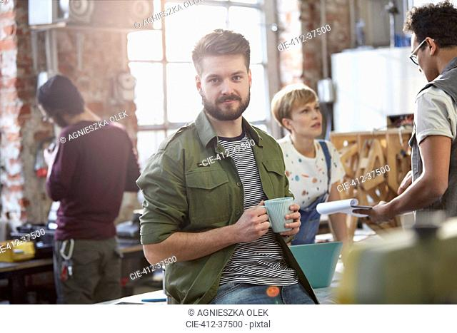 Portrait confident young male designer drinking coffee in workshop