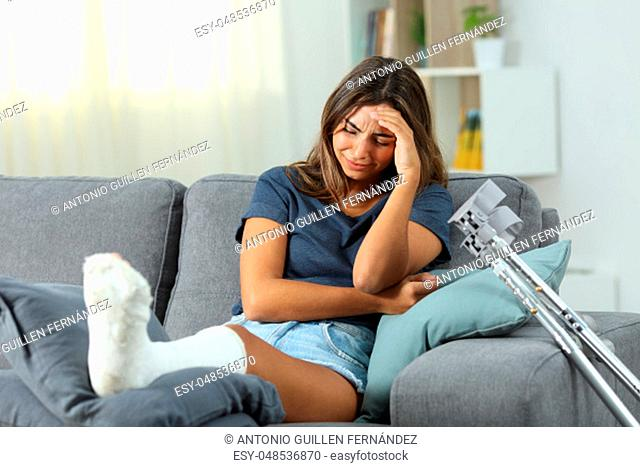 Sad disabled woman complaining alone sitting on a couch in the living room at home