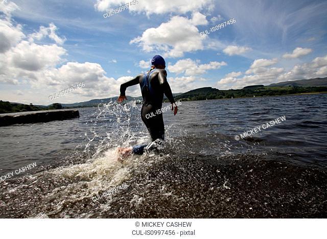 Triathlete swimmer running into water