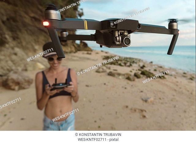 Indonesia, Bali, Nusa Dua, woman flying drone at the beach