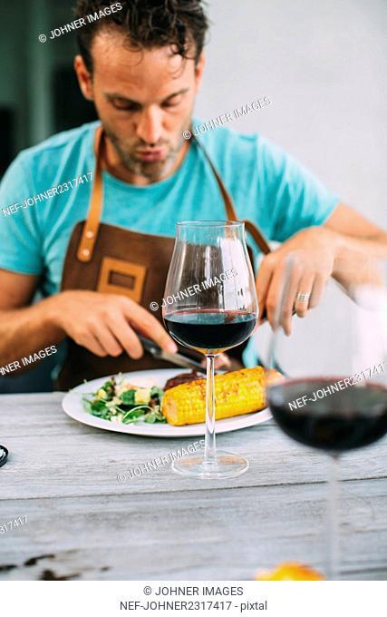 Man eating salad and corn