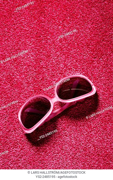 Still life of pink plastic sunglasses lying on red carpet. Copy space above the glasses