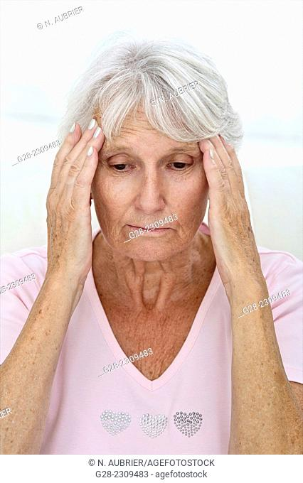 Senior woman in pink suffering from a headache