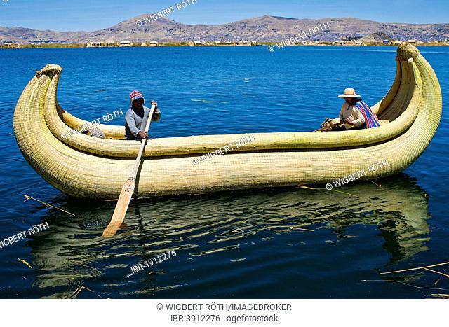 Two local in a traditional rowing boat of Totora reed on Lake Titicaca, Peru