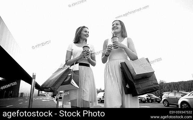 Black and white portrait of two girls with shoppings bags on car parking after doing shopping in mall
