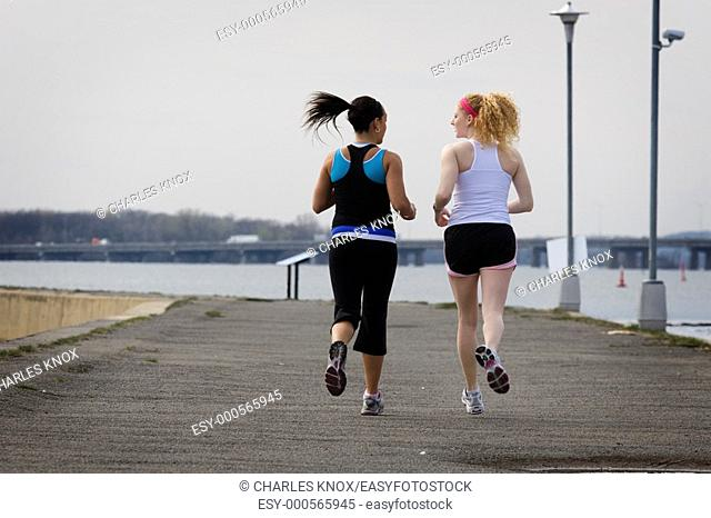 Two young women jogging on cloudy day