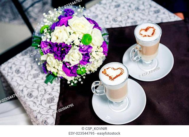 Two cups of coffee with heart on the table, bridal wedding bouquet