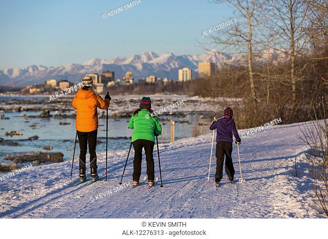 People cross country skiing on the Tony Knowles Coastal Trail near Earthquake Park with Anchorage skyline in the background, Cook Inlet, Southcentral Alaska