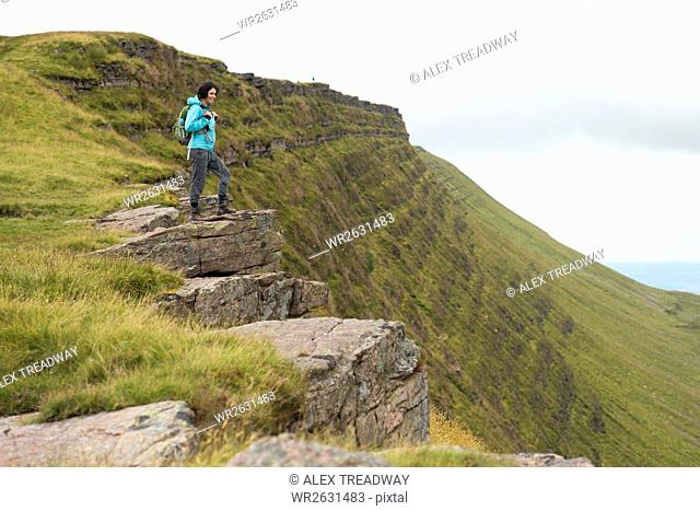 A woman looks out from a ridge while walking to Lyn y Fan Fawr in the Brecon Beacons, South Wales, United Kingdom, Europe