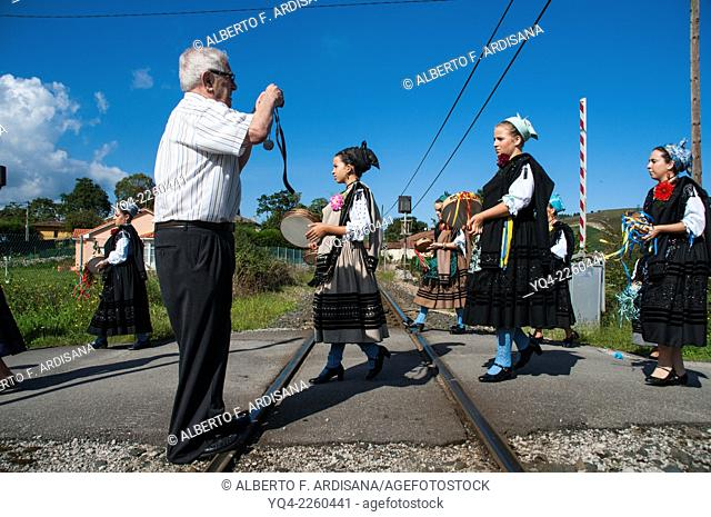 A man taking pictures of the girls in the procession, while crossing the railway line. Llanes, Asturias