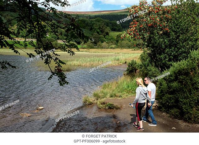 COUPLE STROLLING ON THE BANKS OF THE LOWER LAKE, SITE OF THE RUINS OF THE OLD MONASTERY OF GLENDALOUGH, WICKLOW COUNTY, IRELAND