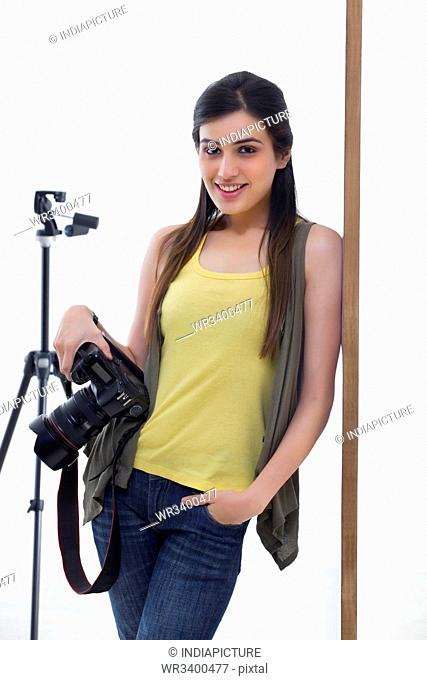 Portrait of young photographer with digital camera leaning against wall
