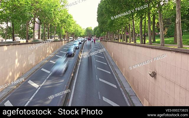 France. Summer day on a green street in Paris. Heavy traffic at the entrance to the tunnel
