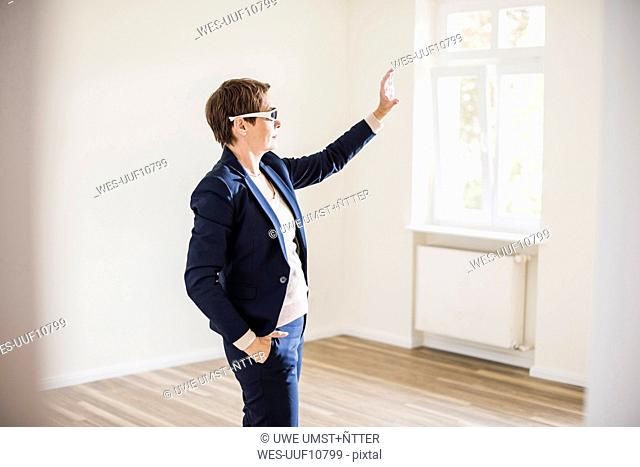 Woman in empty apartment wearing smartglasses