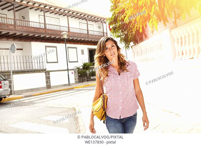 Beautiful young woman 20-24 years old walking down the street and looking at the camera