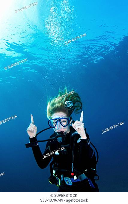 A happy diver doing a decompression stop, or deco stop, a halt in accent from a dive to safely purge absorbed inert gases and avoid decompression sickness
