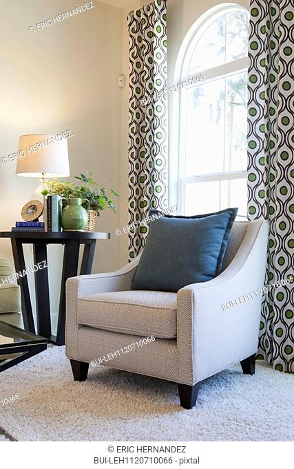 Upholstered armchair with end table by the window at home; San Marcos; California; USA