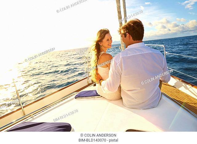 Caucasian couple sitting on yacht deck