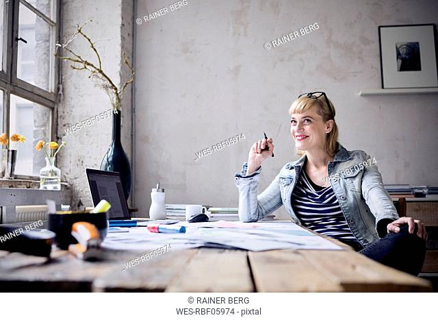 Portrait of laughing woman sitting at desk in a loft
