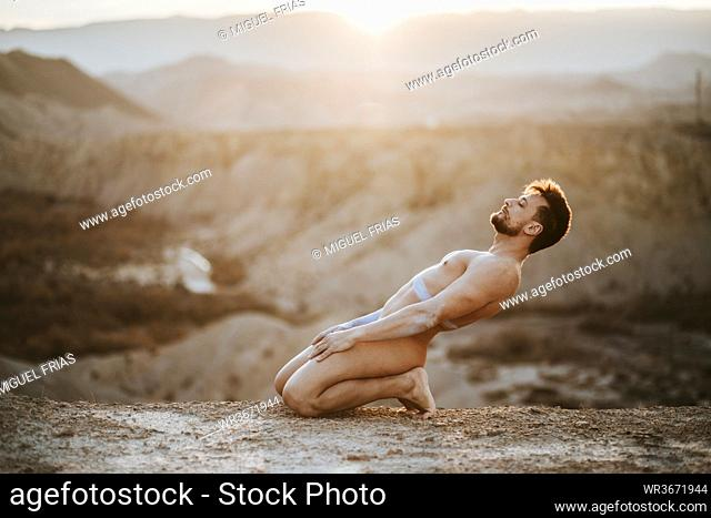 Naked mid adult man kneeling on land at desert during sunset