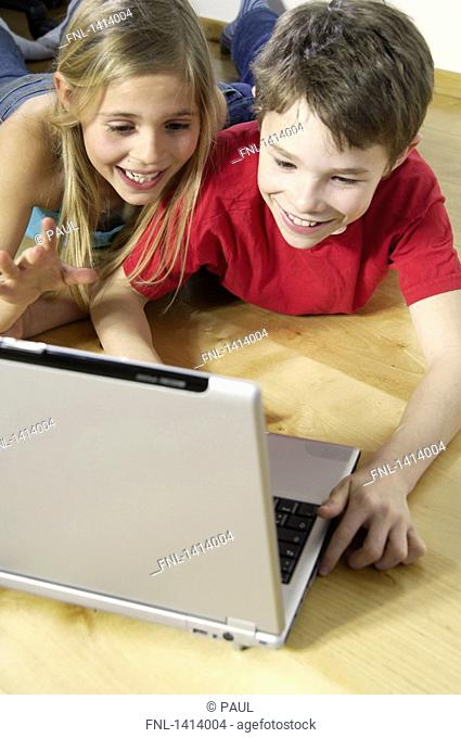 High angle view of brother and sister looking at laptop and smiling