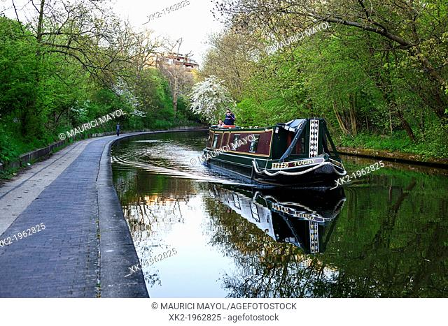 Boat navigating along Regents canal, near Regents Park, London, UK