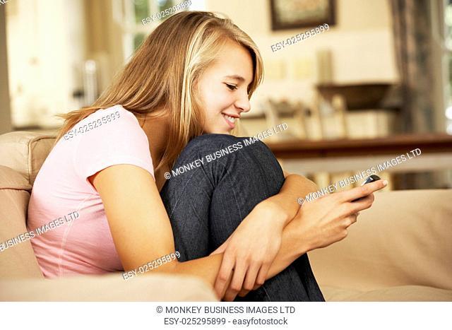 Teenage Girl Sitting On Sofa At Home Texting On Mobile Phone