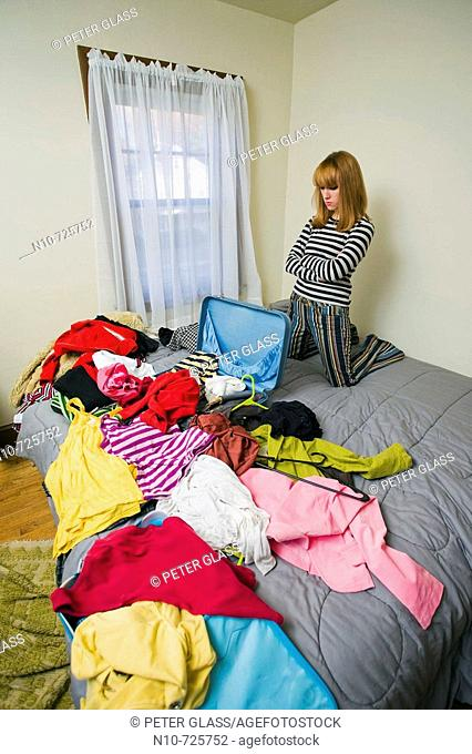Young blond woman, her suitcase in front of her, kneeling on a bed with her clothes scattered about