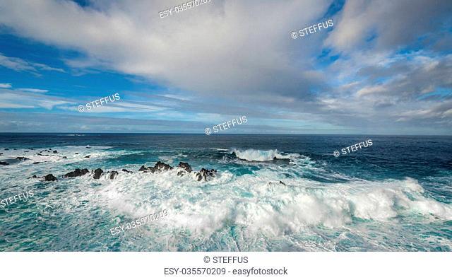 Atlantic ocean seascape. Waves comes to rocky shores with white foam and splashes. Calhau das Achadas, west coast of Madeira island, Portugal