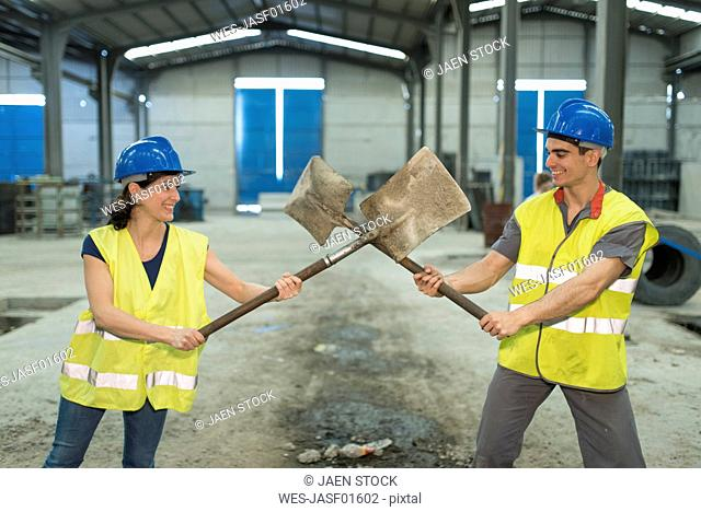 Factory workers playfighting with shovels