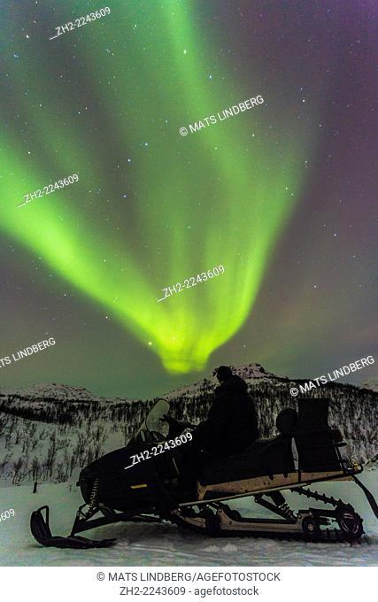Man on snowmobile watching Northern light in Riksgränsen, Kiruna, Swedish lapland