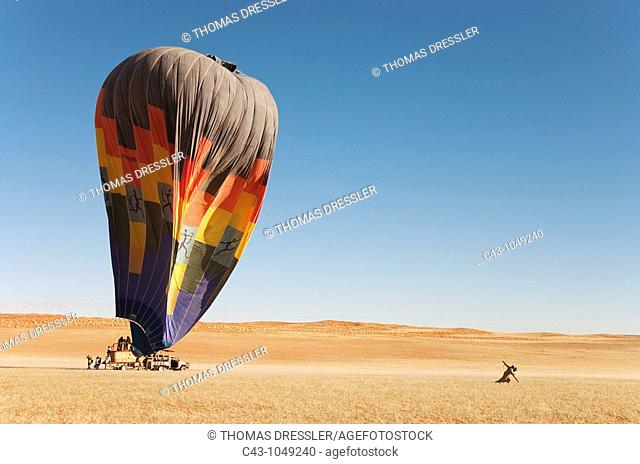 Namibia - After having landed, the ground crew assists the passengers at getting out of the basket of the hot-air balloon while another 2 assistants try to drag...