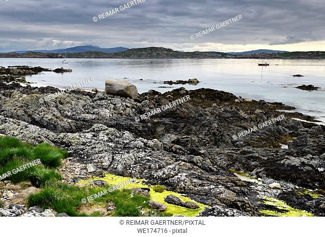 Rocky shore of Isle of Iona with sailboats on Sound of Iona and view of Fionnphort Isle of Mull mountains Inner Hebrides Scotland UK