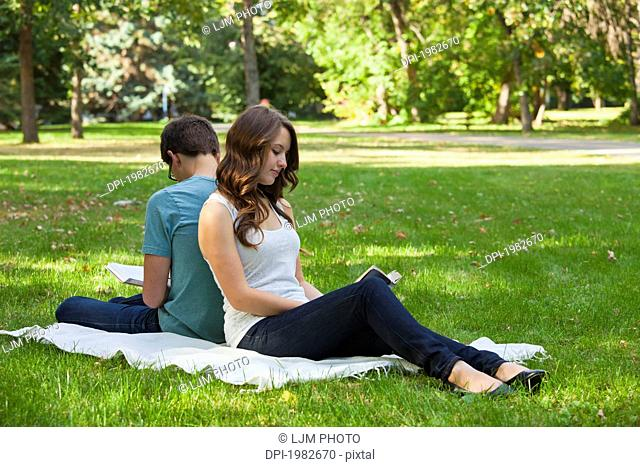 newlywed couple reading together in a park, edmonton alberta canada