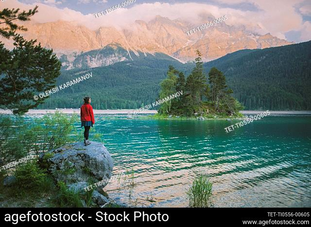 Germany, Bavaria, Eibsee, Young woman standing on rock by Eibsee lake in Bavarian Alps