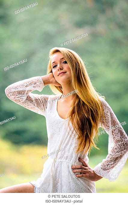 Portrait of teenage girl with long hair posing in park